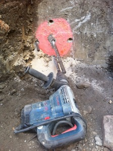 Hammer drilling a hole for the thermo-pex through the foundation.